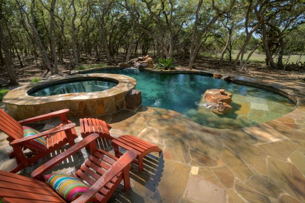 A freeform pool with irregular spa in a natural setting.