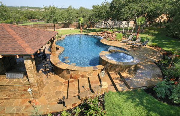 A lower level outdoor kitchen with swim-up bar seating on the inside of the pool.
