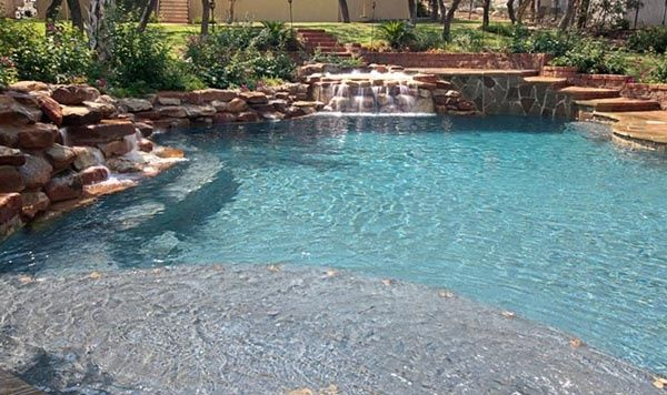 A lagoon pool with with extensive rock work and a large tan ledge.