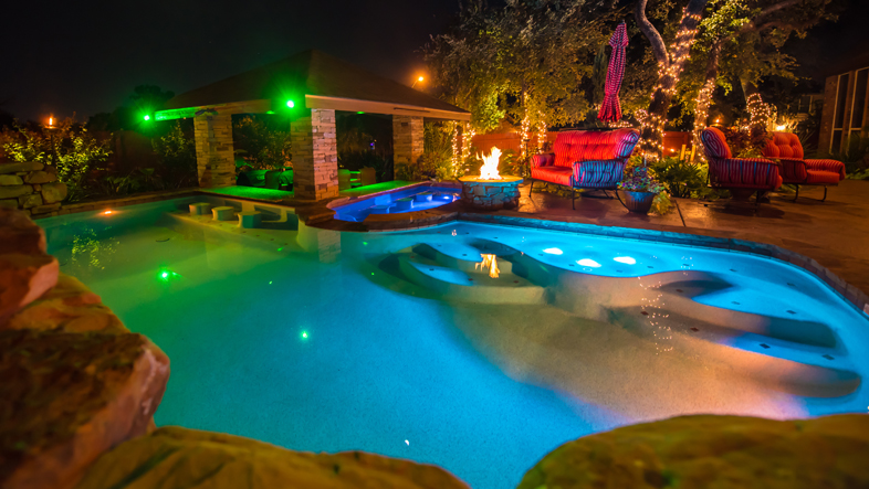 tropical freeform pool with swimup bar, fire pits, rock waterfall